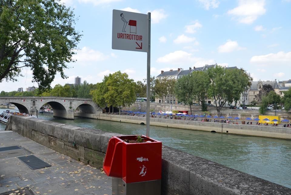 """An open-air urinal """"Uritrottoir"""" stands on the banks of the Seine on the picturesque Saint-Louis Island in Paris. (Photo by Sebastian Kunigkeit/picture alliance via Getty Images)"""