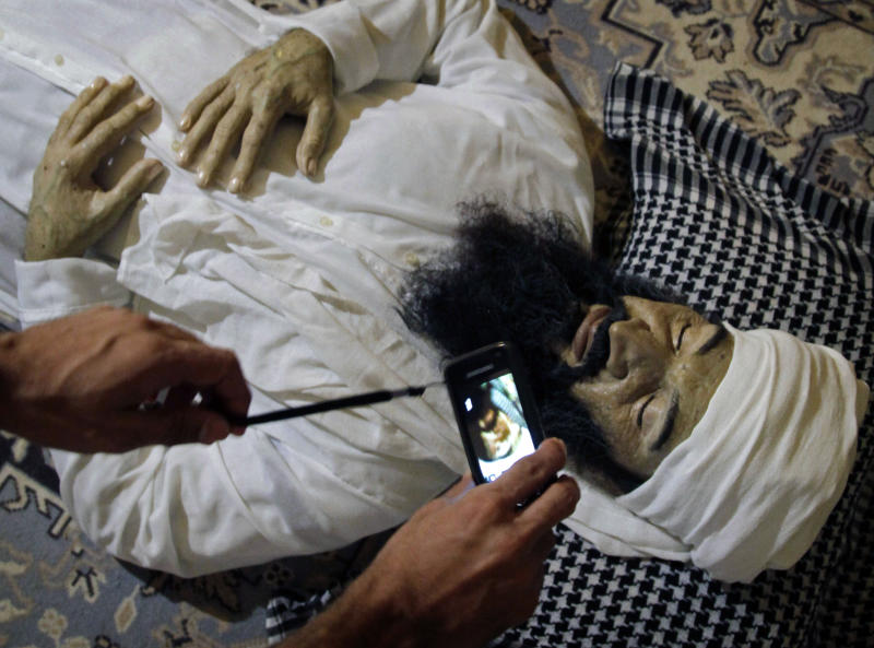 "A student makes a picture with a smart phone of the realistic sculpture of the late al-Qaeda leader Osama bin Laden by artists Alberto Lorente, Manolo Castro and Julio Lorente titled ""He"" that is on display at the Superior Institute of Arts during the 11th Havana Biennial contemporary art exhibition in Havana, Cuba, Thursday, May 10, 2012. (AP Photo/Javier Galeano)"