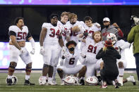 A handful of Stanford players pose for a photo after the team's 31-26 win over Washington in an NCAA college football game Saturday, Dec. 5, 2020, in Seattle. (AP Photo/Elaine Thompson)