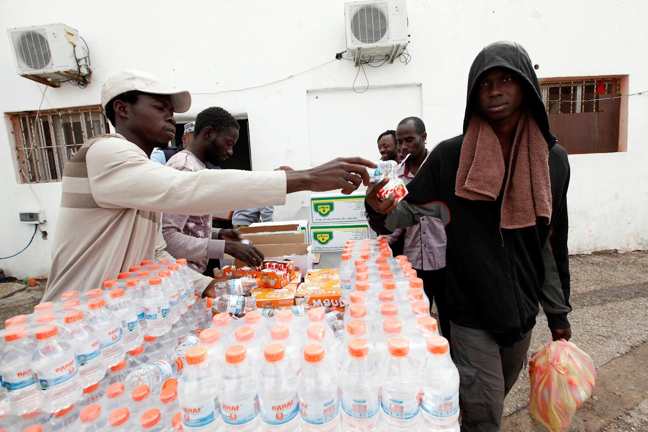 An illegal African migrant receives food and water at a detention camp in Tripoli, Libya, March 22, 2017. REUTERS/Ismail Zitouny