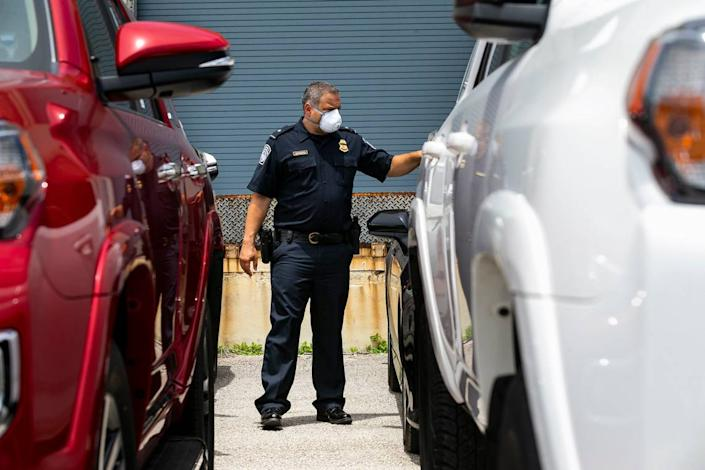 Dylan DeFrancisci, port director for U.S. Customs and Border Protection, looks at more than 80 vehicles seized by Homeland Security Investigations at Port Everglades on Tuesday, July 7, 2020. The vehicles, worth $3.2 million, were being shipped from Port Everglades to Venezuela. The cars, allegedly bought by a ring associated with the government of Venezuelan President Nicolas Maduro, were intercepted by Customs and Border Protection.