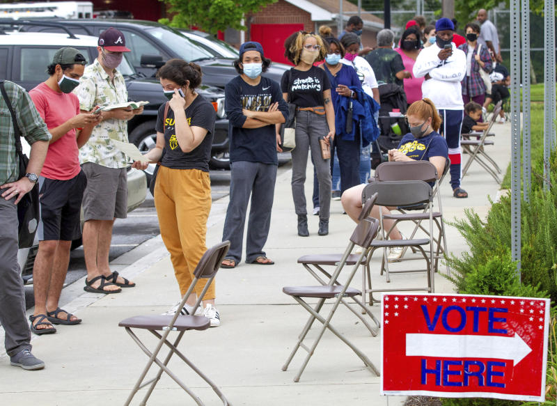 Voters wait in a line that stretched around the Metropolitan Library in Atlanta, Georgia, Tuesday, June 9, 2020. (Steve Schaefer/Atlanta Journal-Constitution via AP)