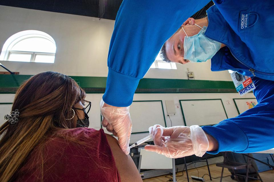 Sucre Lopez receives her second dose of the Moderna Covid-19 vaccine from registered nurse Frederick Morley at a mobile Covid-19 vaccination clinic, run by Hartford Healthcare at Saint Charles Borromeo Catholic Church's McGivney community center in Bridgeport, Connecticut on April 20, 2021. (Joseph Prezioso/AFP via Getty Images)