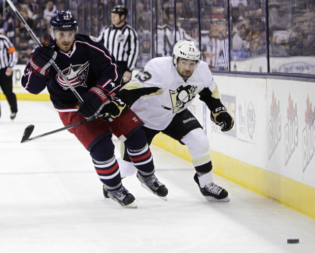 Columbus Blue Jackets' James Wisniewski, left, and Pittsburgh Penguins' Chris Conner chase a loose puck during the first period of an NHL hockey game on Sunday, Dec. 29, 2013, in Columbus, Ohio. (AP Photo/Jay LaPrete)