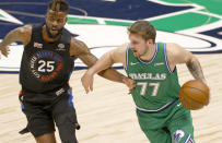 Dallas Mavericks guard Luka Doncic (77) is defended by New York Knicks forward Reggie Bullock (25) during the first half of an NBA basketball game Friday, April 16, 2021, in Dallas. (AP Photo/Ron Jenkins)