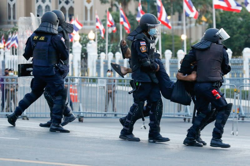 A pro-democracy protester is detained by police officers in front of the Government House during a rally in Bangkok