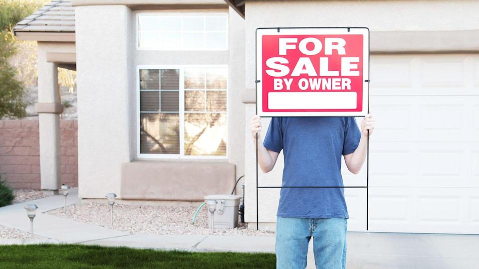 - A photograph of a man standing in front of his house, hiding behind a For Sale sign.