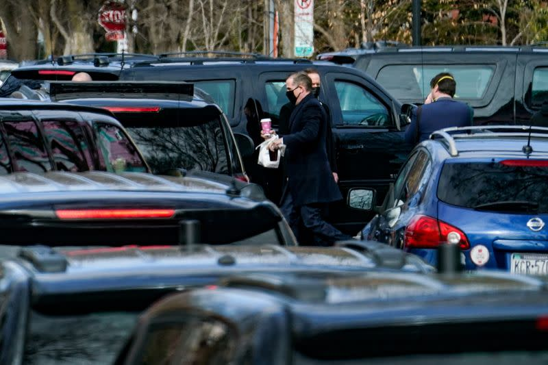 Hunter Biden, son of U.S. President Joe Biden, carries bagels to the presidential motorcade after a visit to Holy Trinity Catholic Church in Washington