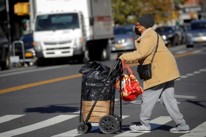 A woman pushes a cart full of free holiday food from the Food Bank For New York City ahead of the Thanksgiving holiday in New York