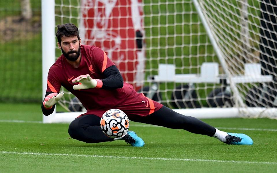 Alisson dives for the ball in training - LIVERPOOL FC