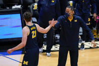 Michigan coach Juwan Howard and guard Franz Wagner (21) celebrate during the first half of the team's NCAA college basketball game against Purdue in West Lafayette, Ind., Friday, Jan. 22, 2021. (AP Photo/Michael Conroy)