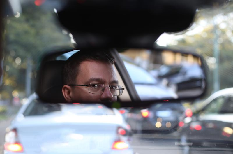 A driver looks in the rear view mirror.