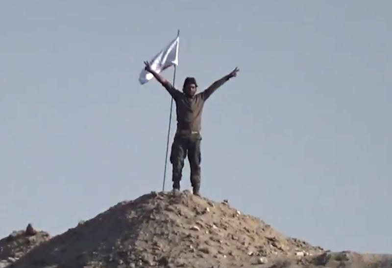 Image grab from video uploaded by Servan Minbec channel on Youtube on January 26, 2015, shows Syrian rebel fighters celebrating after placing a flag of the Fajr al-Hurreya brigade (Dawn of Freedom), on top of a hill in Kobane, know as Ain al-Arab (AFP Photo/)