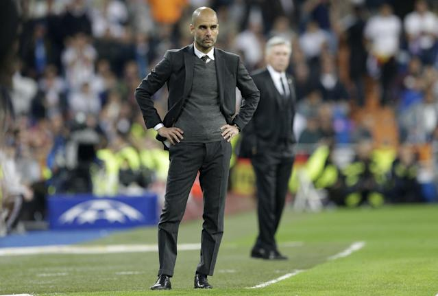 Bayern head coach Pep Guardiola, left, watches the Champions League semifinal first leg soccer match between Real Madrid and Bayern Munich at the Santiago Bernabeu stadium in Madrid, Spain, Wednesday, April 23, 2014. (AP Photo/Paul White)