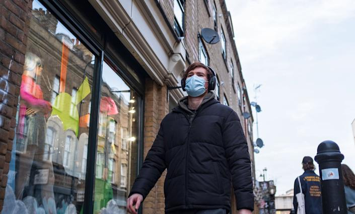 A man wearing a face mask walking on the street in London Prime Minister Boris Johnson unveils plan to end England restrictions. A new four-step plan to ease England's lockdown could see all legal limits on social contact lifted by 21 June, if strict conditions are met. (Photo by May James / SOPA Images/Sipa USA)