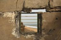 The sea is seen through a window of an abandoned house on the beach of Afidegnigban