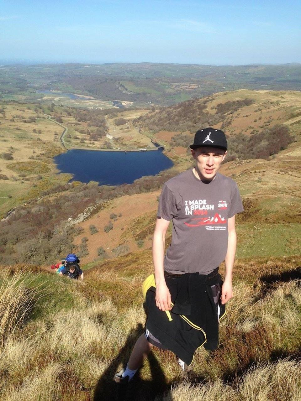 Jack Bayley, 20, stands on a hill, wearing a grey t-shirt and a black cap