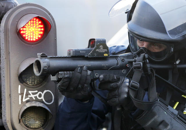 A riot police officer aims at a yellow vests demonstration on the Champs Elysees avenue Saturday, March 16, 2019 in Paris. French yellow vest protesters clashed Saturday with riot police near the Arc de Triomphe as they kicked off their 18th straight weekend of demonstrations against President Emmanuel Macron. (AP Photo/Christophe Ena)
