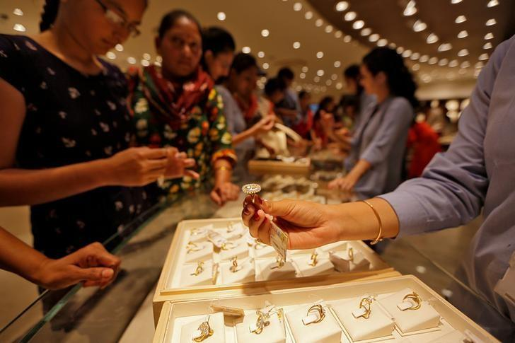 FILE PHOTO - A sales person shows a gold ring to customers at a jewellery showroom during Dhanteras, a Hindu festival associated with Lakshmi, the goddess of wealth, in Ahmedabad