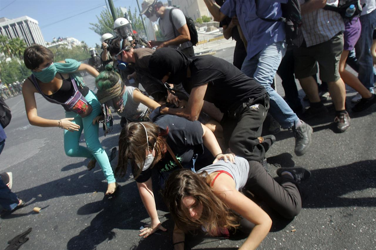 Protestors fall down in the street during clashes with riot police officers near Syntagma square as a 24-hour labour strike is in effect , on September 26, 2012 in Athens. Today marks Greece's first big anti-austerity strike since the coalition government took power in June.  (Photo by Milos Bicanski/Getty Images)