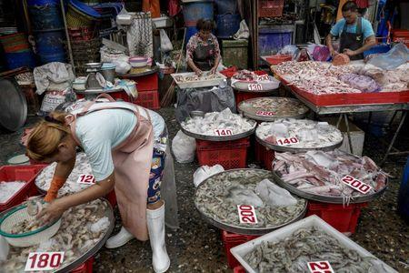 Vendors sort fish and other seafood at a market in Bangkok