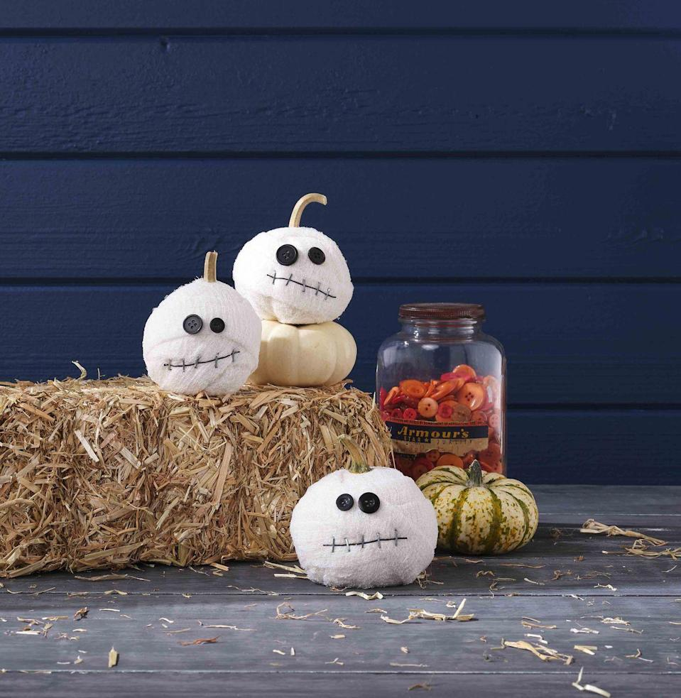 <p>These mummies are just as cute as a button!<br><strong><br>Make the pumpkin:</strong> Wrap a small white pumpkin with strips of gauze, holding strips in place where necessary with hot-glue. Attach two differently sized black buttons with hot-glue to create eyes. Tack down a length of thin black twine with staple-gun staples to create a mouth.<br></p>