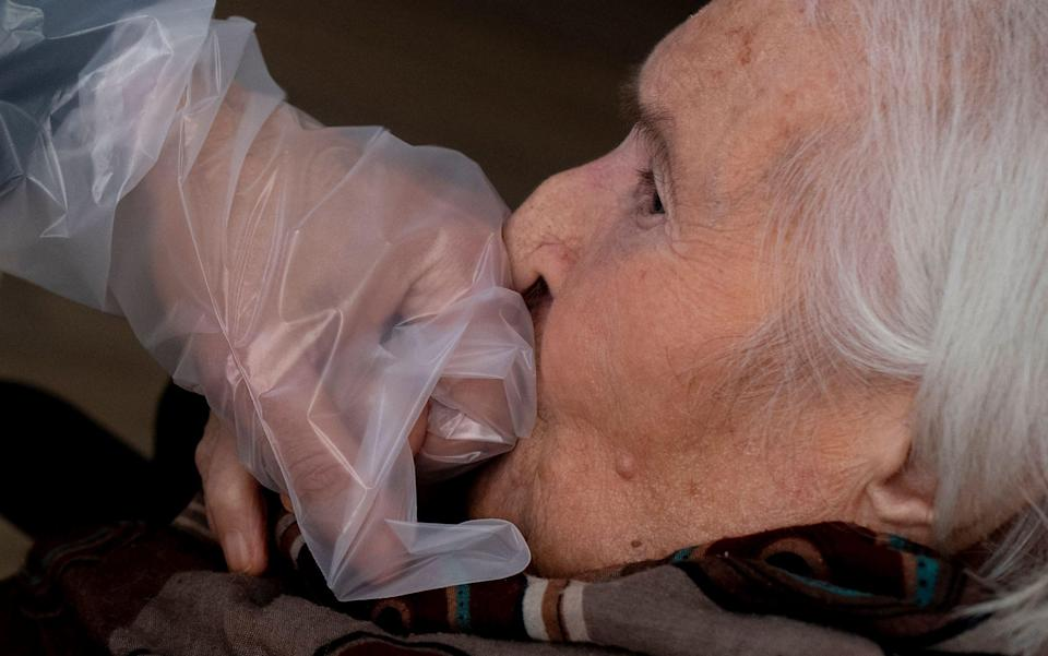 "An elderly resident of the Villa Sacra Famiglia nursing home in Rome kisses her grandson's hand through a plastic screen in a so-called ""Hug Room"" - TIZIANA FABI/AFP"