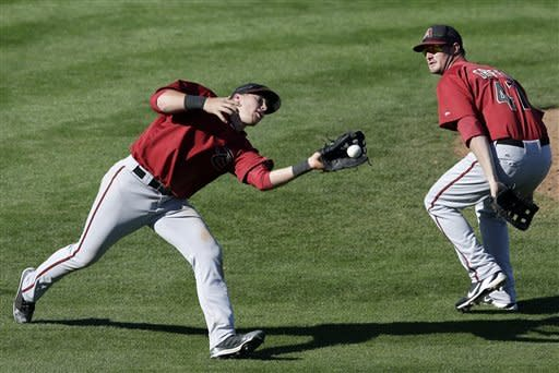 Arizona Diamondbacks third baseman Brandon Drury, left, bobbles and drops a pop fly hit by Seattle Mariners' Julio Morban as Diamondbacks shortstop Jon Griffin, right, looks on during the ninth inning in an exhibition spring training baseball game Tuesday, March 12, 2013, in Peoria, Ariz. (AP Photo/Gregory Bull)