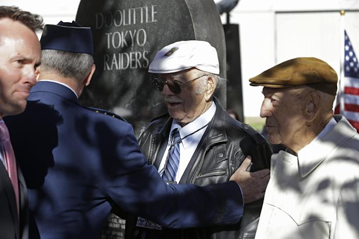 Two of the four surviving members of the 1942 raid on Tokyo led by Lt. Col. Jimmy Doolittle, Edward Saylor, center, and Richard Cole, right, are thanked by Gen. Mark Welsh III, Chief of Staff of the US Air Force, and Eric Fanning, left, acting Secretary of the US Air Force, Saturday, Nov. 9, 2013, at a monument marking the raid at the National Museum of the US Air Force in Dayton, Ohio. (AP Photo/Al Behrman)