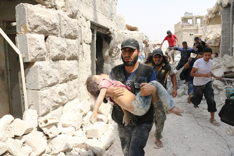 A Syrian man carries a wounded child following a barrel bomb attack on the Bab al-Nayrab neighbourhood of Aleppo on August 25, 2016 (AFP Photo/Ameer Alhalbi)