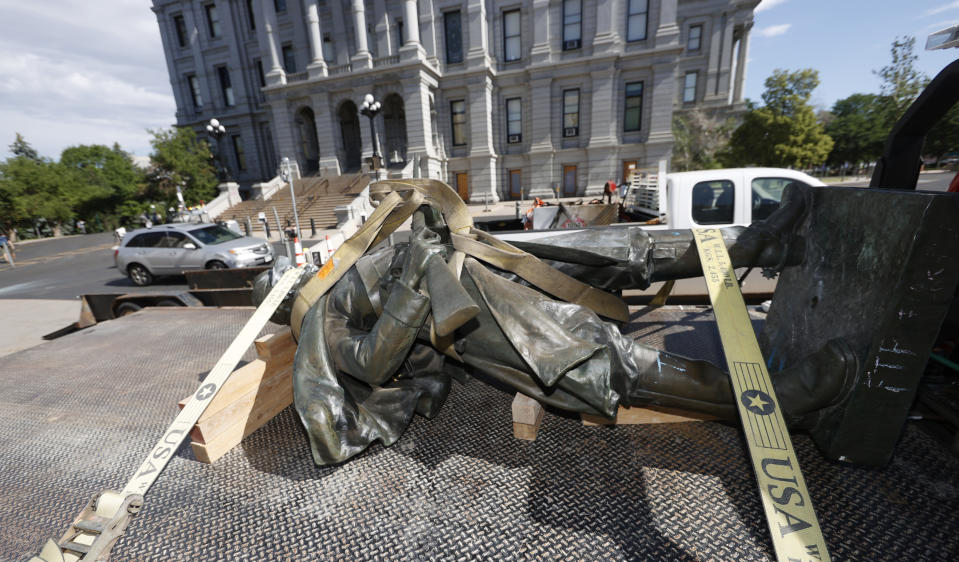 FILE - In this June 25, 2020 file photo, the Civil War Monument statue is shown loaded on the back of a flatbed truck after it was toppled from its pedestal in front of the State Capitol in Denver. The monument, which portrays a Union soldier and was erected in 1909, was targeted during demonstrations over the death of George Floyd before the statue was pulled down by four individuals. On Thursday, Feb. 25, 2021, Colorado lawmakers will discuss what to put in place of the statue. (AP Photo/David Zalubowski, File)