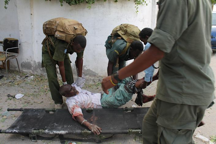 Somali soldiers carry a wounded civilian at the entrance of Mogadishu's court complex after being injured during a siege by militants in Mogadishu, Somalia, Sunday, April 14, 2013. Militants launched a serious and sustained assault on Mogadishu's main court complex Sunday, detonating at least two blasts, taking an unknown number of hostages and exchanging extended volleys of gunfire with government security forces, witnesses said..(AP Photo/Farah Abdi Warsameh)