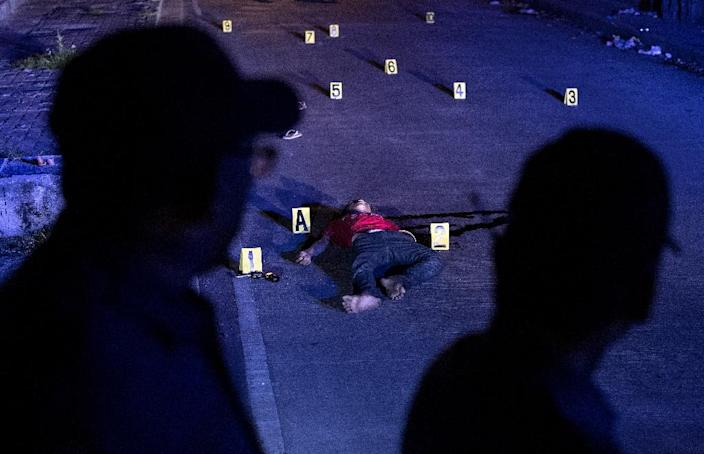 The body of an alleged drug dealer killed during a police anti-drug operation is seen on the ground in Manila on August 18, 2017 (AFP Photo/Noel Celis)