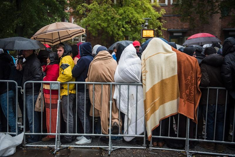 Immigrants shelter from the elements under blankets and umbrellas as they queue to be allowed into a registration centre at the Office of Health and Social Affairs in Berlin