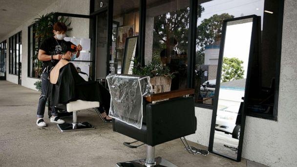PHOTO: Hairstylist Travis Vu gives a haircut to Minh Dao at his outdoor hair salon in Fountain Valley, Calif., July 22, 2020. (Jae C. Hong/AP)