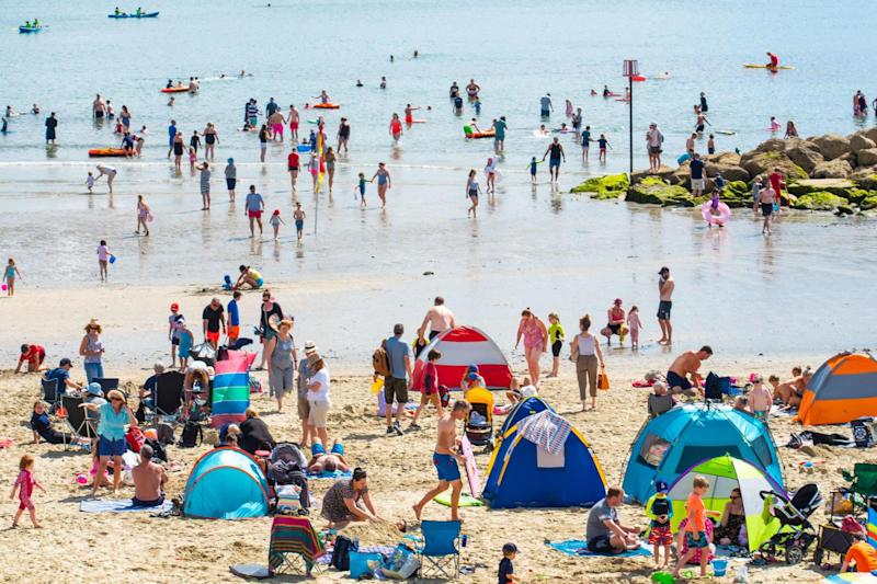 Crowds of holidaymakers and sunseekers flock to the packed beach at the seaside resort of Lyme Regis to soak up the sunshine: Celia McMahon / Alamy Live News