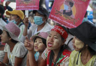 Anti-coup protesters display an image of protester who was shot and killed by Myanmar security forces during a protest two-days earlier as they gather to protest in Yangon, Myanmar Tuesday, Feb. 23, 2021. Protesters gathered in Myanmar's biggest city despite the ruling junta's threat to use lethal force against people who join a general strike against the military's takeover three weeks ago. (AP Photo)