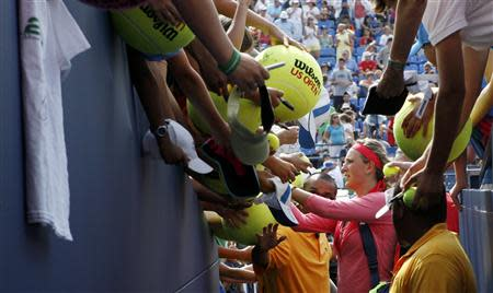 Victoria Azarenka of Belarus signs autographs for fans after defeating Alize Cornet of France in their match at the U.S. Open tennis championships in New York August 31, 2013. REUTERS/Kena Betancur