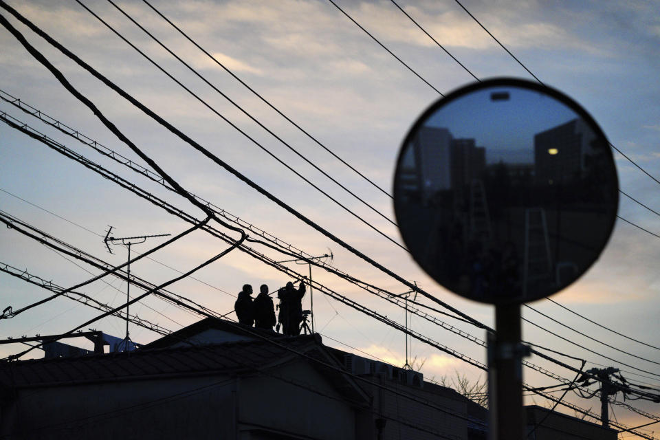 A TV crew team stands by on a rooftop overlooking the Tokyo Detention Center where former Nissan chairman Carlos Ghosn and another former executive Greg Kelly are being detained in Tokyo Thursday, Dec. 20, 2018. (AP Photo/Eugene Hoshiko)