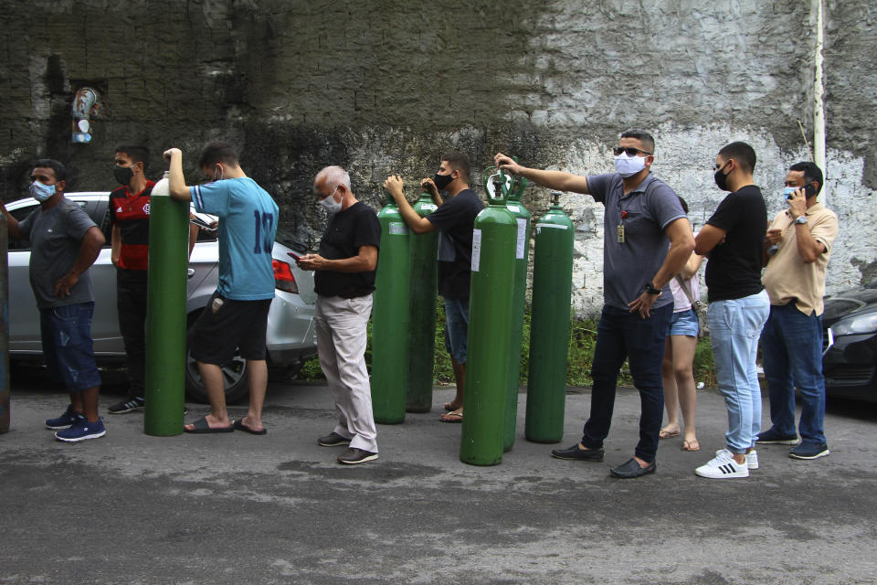 Family members of patients hospitalized with COVID-19 line up with empty oxygen tanks in an attempt to refill them, outside the Nitron da Amazonia company, in Manaus, Amazonas state, Brazil, Friday, Jan. 15, 2021. Doctors in the Amazon rainforest's biggest city are having to choose which COVID-19 patients can breathe amid dwindling oxygen stocks and an effort to airlift some of the infected to other states. (AP Photo/Edmar Barros)
