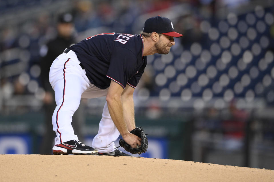 Washington Nationals starting pitcher Max Scherzer stretches on the mound during the first inning of the team's baseball game against the San Francisco Giants, Friday, June 11, 2021, in Washington. Scherzer left the game with an injury. (AP Photo/Nick Wass)