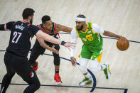 Utah Jazz guard Mike Conley (10) drives the ball on Portland Trail Blazers center Jusuf Nurkic (27) as guard CJ McCollum, rear, also defends during the first half of an NBA basketball game Thursday, April 8, 2021, in Salt Lake City. (AP Photo/Isaac Hale)