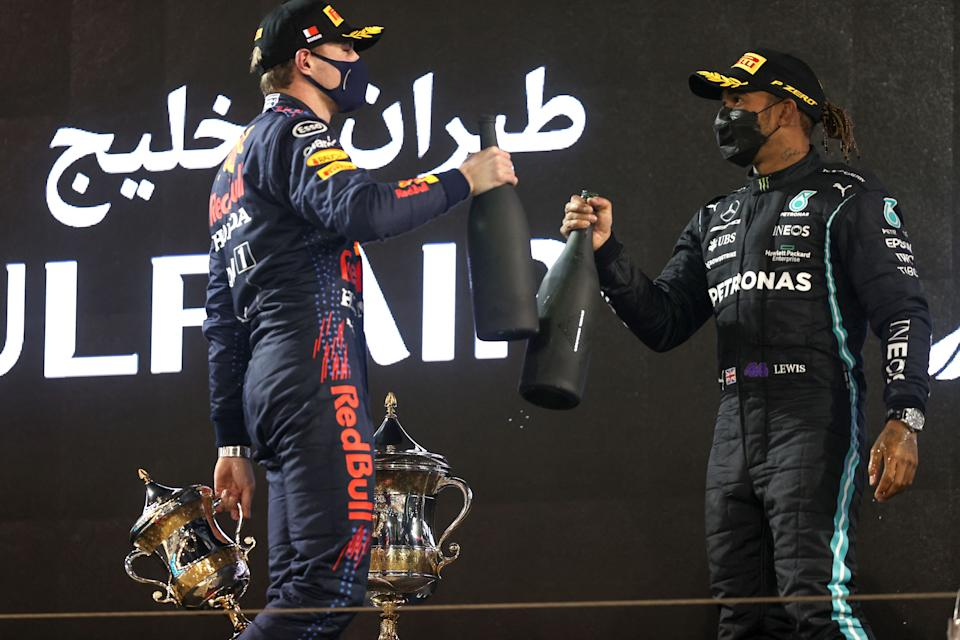 Red Bull's Dutch driver Max Verstappen greets Mercedes' British driver Lewis Hamilton on the podium after the Bahrain Formula One Grand Prix at the Bahrain International Circuit in the city of Sakhir on March 28, 2021. (Photo by Lars Baron / various sources / AFP) (Photo by LARS BARON/AFP via Getty Images)