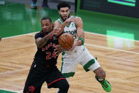 Toronto Raptors guard Norman Powell (24) and Boston Celtics forward Jayson Tatum battle for the ball during the first half of an NBA basketball game, Thursday, March 4, 2021, in Boston. (AP Photo/Charles Krupa)