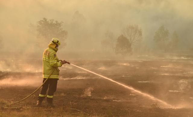 "A firefighter defends a property from a bushfire at Hillville near Taree, 350km north of Sydney on November 12, 2019. - A state of emergency was declared on November 11 and residents in the Sydney area were warned of ""catastrophic"" fire danger as Australia prepared for a fresh wave of deadly bushfires that have ravaged the drought-stricken east of the country. (Photo by PETER PARKS / AFP) (Photo by PETER PARKS/AFP via Getty Images)"