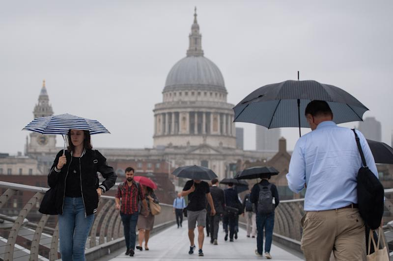 Pedestrians shelter under umbrellas as they cross the Millennium Bridge in central London, during a downpour of rain, as more rainy weather and thunderstorms brought further flood warnings across the UK. Picture date: Monday August 5, 2019. See PA story WEATHER Rain. Photo credit should read: Dominic Lipinski/PA Wire (Photo by Dominic Lipinski/PA Images via Getty Images)