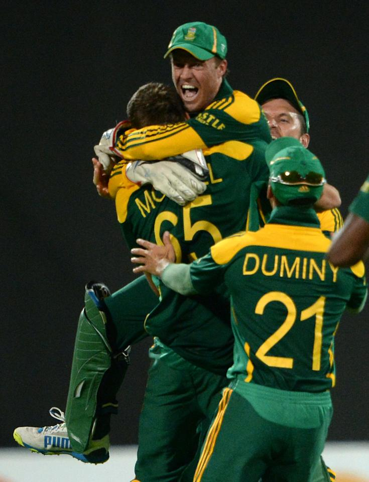 South African captain AB de Villiers (C) celebrates with teammates after winning the first one-day match against Pakistan in Sharjah Cricket Stadium in Sharjah on October 30, 2013. South African captain AB de Villiers won the toss and decided to bat in the first of five one-day internationals against Pakistan in Sharjah. AFP PHOTO/ Asif HASSAN        (Photo credit should read ASIF HASSAN/AFP/Getty Images)