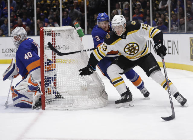 New York Islanders' Mathew Barzal (13) defends Boston Bruins' Charlie Coyle (13) as goaltender Robin Lehner (40) watches during the first period of an NHL hockey game Tuesday, March 19, 2019, in Uniondale, N.Y. (AP Photo/Frank Franklin II)