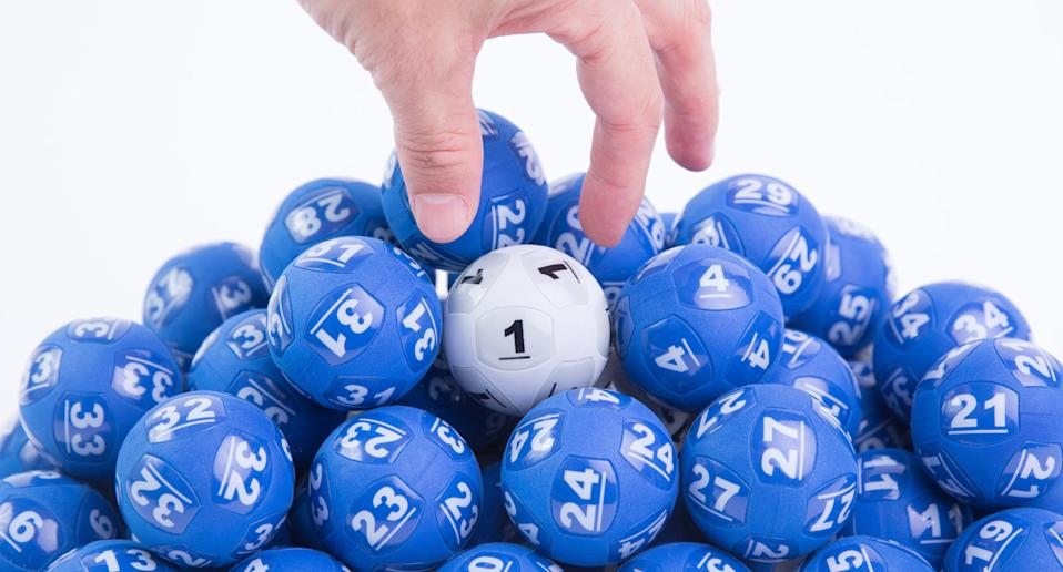 A pile of Powerballs are pictured, with a hand reaching down to select one.