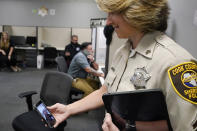 In this Friday, Aug. 13, 2021, photo Sheriff's Police Sgt. Bonnie Busching holds a cellphone as she tests a virtual meeting with mental health professional at the Cook County Sheriff's Office in Chicago. The Cook County Sheriff's department officers are hitting the streets with tablets that can connect people in distress immediately with mental health professionals. And Cook County Sheriff Tom Dart says the Treatment Response Team has been successful bringing calm to the tensest of domestic situations involving people at risk of hurting themselves or others. (AP Photo/Nam Y. Huh)